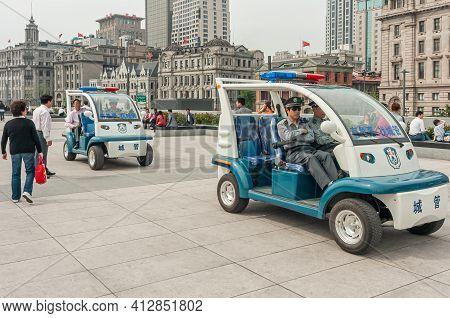 Shanghai, China - May 4, 2010: 2 Blue-white Electric Police Vehicles On Boardwalk Along Bund. Iconic