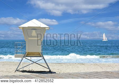Lifeguard stand on a beach with the ocean and waves and a blue cloudy sky and sail boat.
