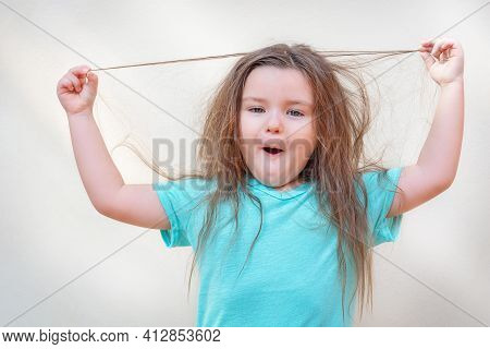 Portrait Of A Funny Child. Girl Dabbles In Hair