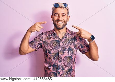 Handsome blond man on vacation wearing casual shirt and sunglasses over pink background smiling cheerful showing and pointing with fingers teeth and mouth. Dental health concept.