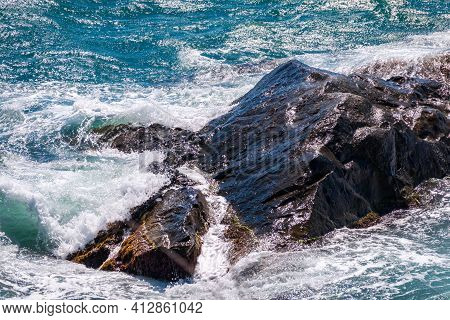 Sea Water Beats Against Rocks. Sea Waves Of Dark Water Beat Against The Coastal Rocks. An Infinite N