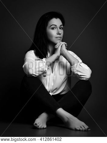 Calm Wise Beautiful Adult Brunette Woman In White Shirt And Pants Sits Barefooted On Floor Holding H