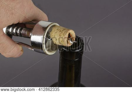 Wine Bottle, Hand With A Corkscrew And A Broken Cork On A Gray Background. A Man's Hand Holds A Cork