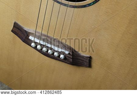 Fragment Of An Acoustic Six-string Guitar. Yellow Guitar With Strings And Bridge. Indoors. Close-up.