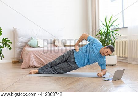 Middle-aged Man In Front Of Laptop Monitor Doing A Side Plank Exercise. He Follows The Guidance Of H