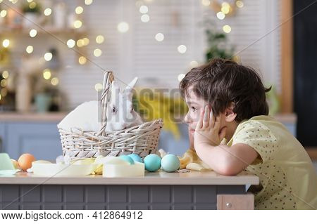 Happy Easter. Child Boy In Bunny Ears Plays With Decorated Eggs And Hare Sits In A Wicker Basket On