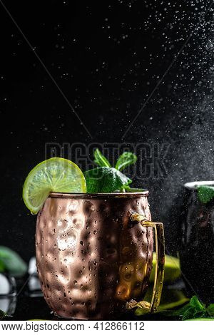 Moscow Mule Cocktail With Lime, Ginger Beer, Vodka And Mint Garnish. Splashes And Ice Frozen Motion.