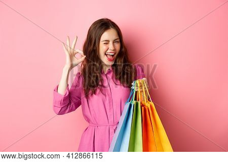 Young Happy Woman Shopper Showing Okay Sign, Winking Pleased With Good Discounts, Buying Staff On Sa