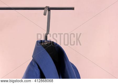 Blue Mens Shirt On Brown Plastic Hanger On Light Background With Copy Space