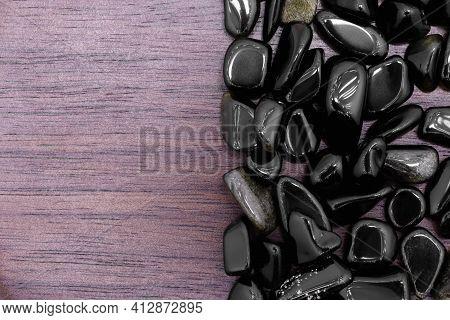 Gold Obsidian Rare Jewel On Half Brown Varnished Wood Texture. Pile Mineral Pebbles Background. Plac