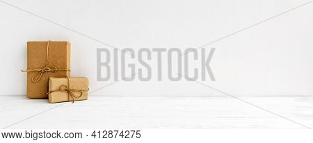 Fashionable Stock Background - On A White Background Gift Boxes In Kraft Paper. Greeting Background