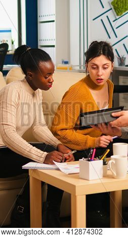 Multiethnic Team Analysing Informations From Tablet Discussing Sitting On Couch Brainstorming On New