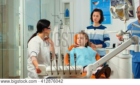 Stomatologist Doctor Explaining To Mother The Dental Process Of Intervention For Teeth Problems Of K