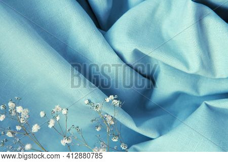 Draped Beautiful Folds Of Blue Natural Fabric Background With Shadows And White Gypsophila Flowers.