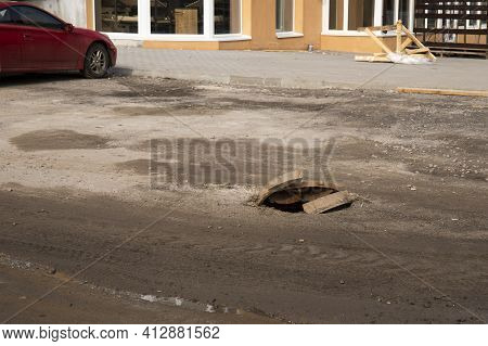 A Broken Road With Open Sewer Hatch. Danger To Cars And Pedestrians.