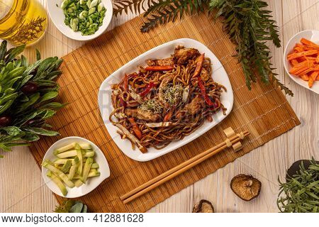 Stir Fry Noodles With Chicken And Vegetables In A White Plate