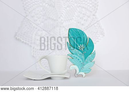 Blue Gingerbread In Shape Of Feather Stands Next To Mug On White Background. Sweet Pastries. Dessert