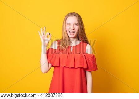 Cute Girl Blinks Eye, Makes Okay Gesture, Demonstrates Her Agreement, Feels Happy, Wears Red Dress,