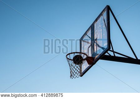 A Basketball In A Hoop Against A Blue Sky.