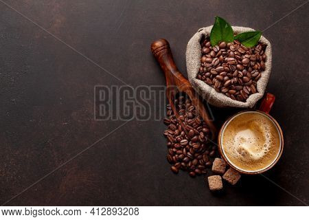 Roasted coffee beans, brown sugar and cup of hot espresso coffee. Top view flat lay with copy space