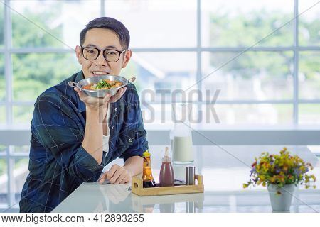 Young Man Wearing Glasses Holding The Fried Egg Served On A Pan With Colorful Toppings Served On A P