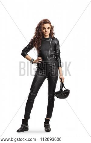 Full length portrait young woman with curly hair holding a biker helmet and wearing a leather jacket isolated on white background