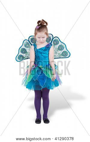 Frowning girl in carnival costume stands looking from under her brows and clenching her fists