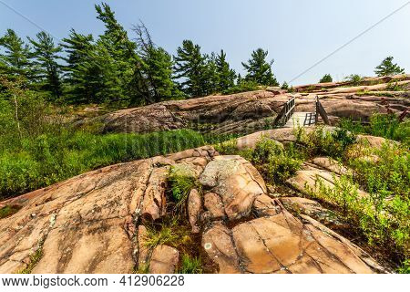 A Wooden Footbridge Over Rugged Granite Rocks On A Trail Along The Coast Of Georgian Bay. Killarney