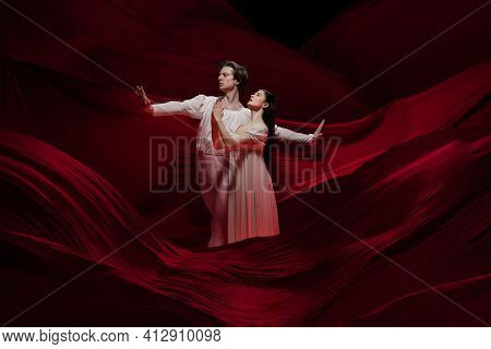 Legendary. Young And Graceful Ballet Dancers On Red Cloth Background In Classic Action. Art, Motion,