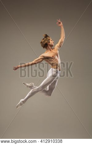 Muscular. Young And Graceful Ballet Dancer Isolated On Studio Background In Flight, Jump. Art, Motio