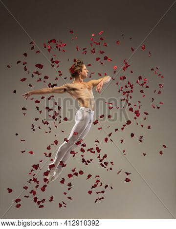 Loving. Young And Graceful Ballet Dancer On Studio Background In Flight, Jump With Rose Petals. Art,