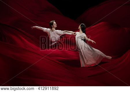 Light. Young And Graceful Ballet Dancers On Red Cloth Background In Classic Action. Art, Motion, Act