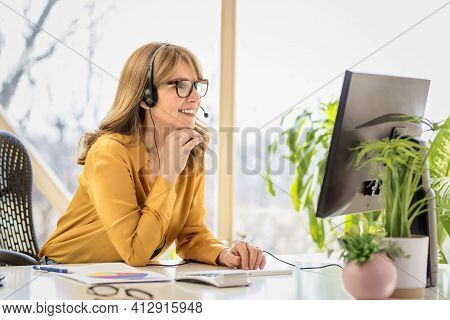 Happy Mature Businesswoman In Headset Speaking By Conference Call While Looking At Computer. Home Of