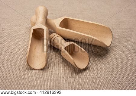 Wooden Scoops For Bulk Products. New Wooden Scoop For Bulk Products And Spices On Sackcloth Backgrou