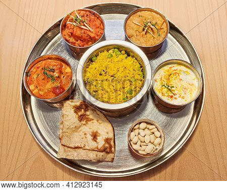 Typical Indian Dish Thali. A Set Of Vegetarian Dishes On One Large Round Plate. On This Dish: Roti,