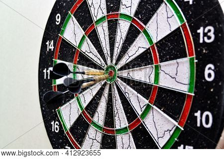 Three Darts Hit The Center Of The Board While Playing Darts.