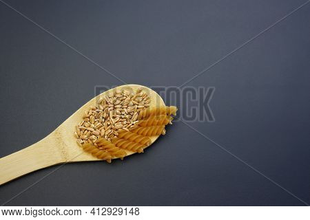Fusilli Pasta And Spelled In A Wooden Spoon On A Gray Background. Spelled Pasta.