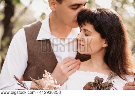 A Man Embraces A Girl With A Bouquet In Her Hands. Gentle Embrace Of Lovers