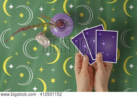 Hands Of Young Woman With Golden Nail Polish Holding Three Tarot Or Oracle Cards, On A Green Stars A