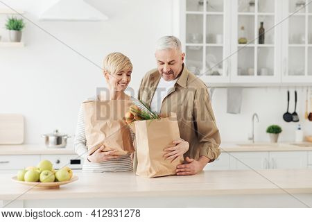 Ordering Food Online. Senior Couple Arriving From Supermarket With Grocery Bag And Unpacking In Kitc