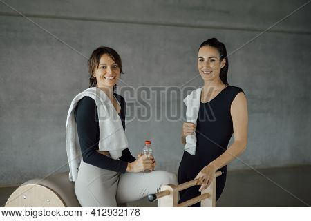 Smiling Caucasian Fit Women In Sport Clothing Looking At Camera In A Gym, Fitness Center. Female Aer