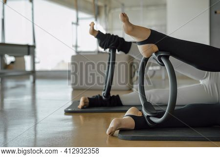 Detail Of Two Female Pair Of Bare Feet With Pilates Yoga Ring, Magic Circle. Aerobic Class In A Gym,