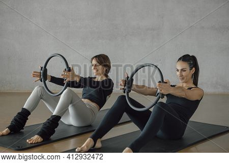 Smiling Brunette Female Coach Showing A Woman To Practice Pilates Stretching Exercise With Magic Cir