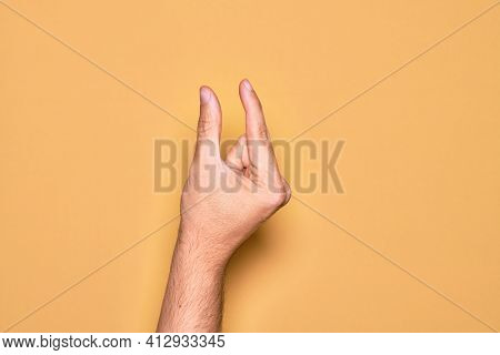 Hand of caucasian young man showing fingers over isolated yellow background picking and taking invisible thing, holding object with fingers showing space