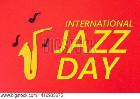International Jazz Day. Silhouette Of A Saxophone From Which Melodies Flew Out, On A Red Background,