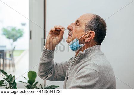 Senior Man Sitting, Self Test For Covid-19 At Home With Antigen Test Kit. Coronavirus Nasal Swab Tes