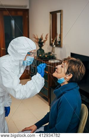 Health Professional In Ppe, Face Mask And Shield, Introducing A Nasal Swab To A Senior Female Patien