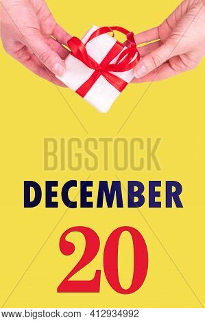 December 20th. Festive Vertical Calendar With Hands Holding White Gift Box With Red Ribbon And Calen