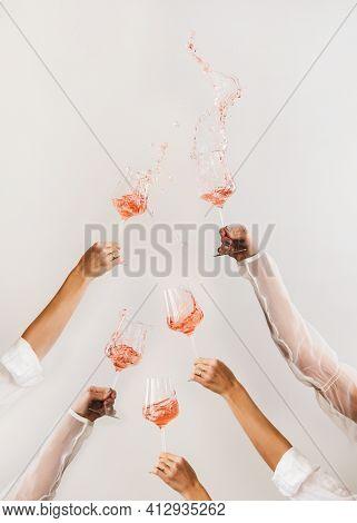 Female Hands Swirling Glasses Of Rose Wine Making Splashes
