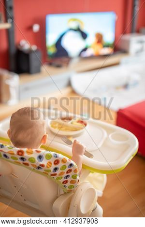 Baby Girl Watching Cartoons On Tv And Eating Balanced Meal